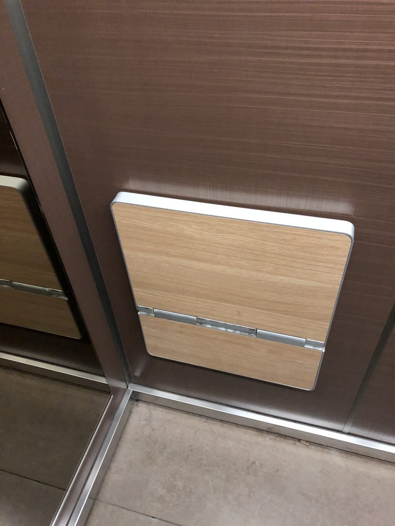 View of a folding seat attached to the wall of an elevator. The seat folded up.