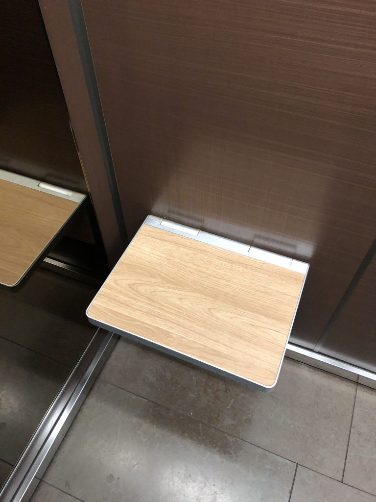 View of a folding seat in an elevator. The seat is folded down for use.