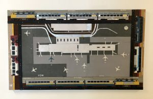 Made of pieces of thin sheet metal and rivets, this touchable art work displays the Ottawa International Airport viewed from above. The airport is framed at the top and bottom by train cars and the sides by inner and inter city buses.